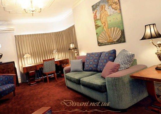 прямой зеленый диван с синими подушками для гостиной