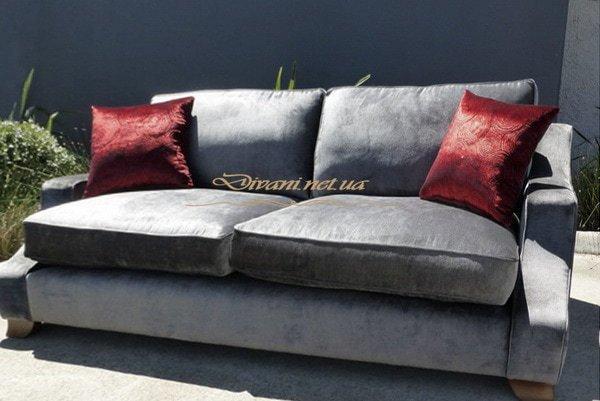 прямой синий диван с красными подушками