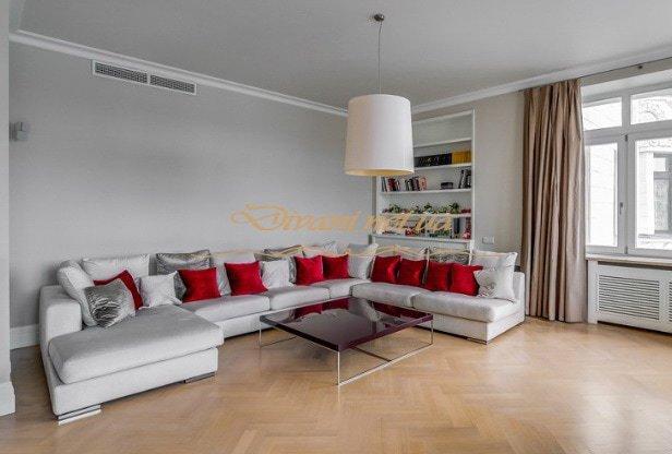 белый п образный диван с красными подушками